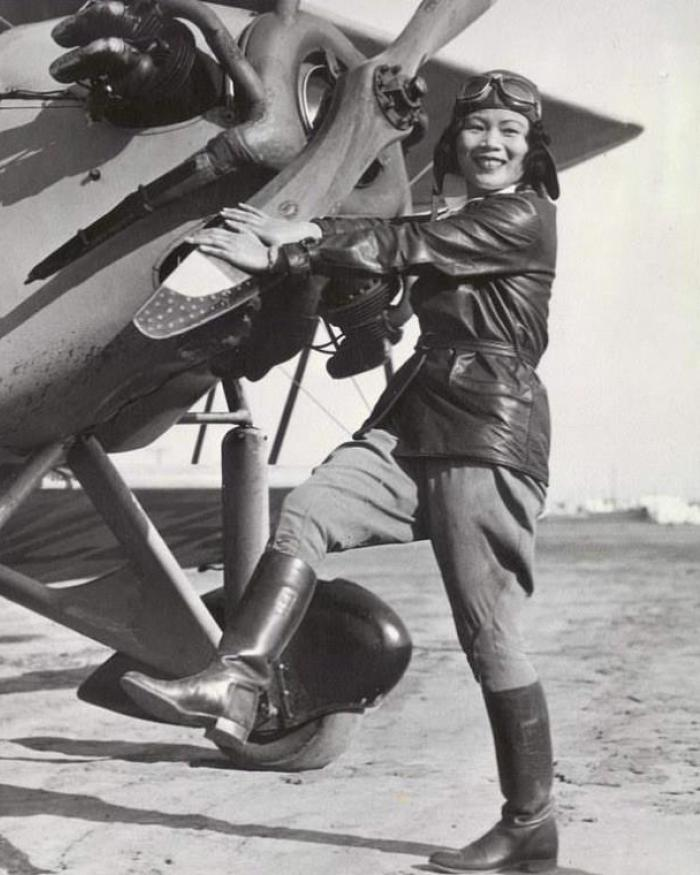 A woman stands in front of a propeller.