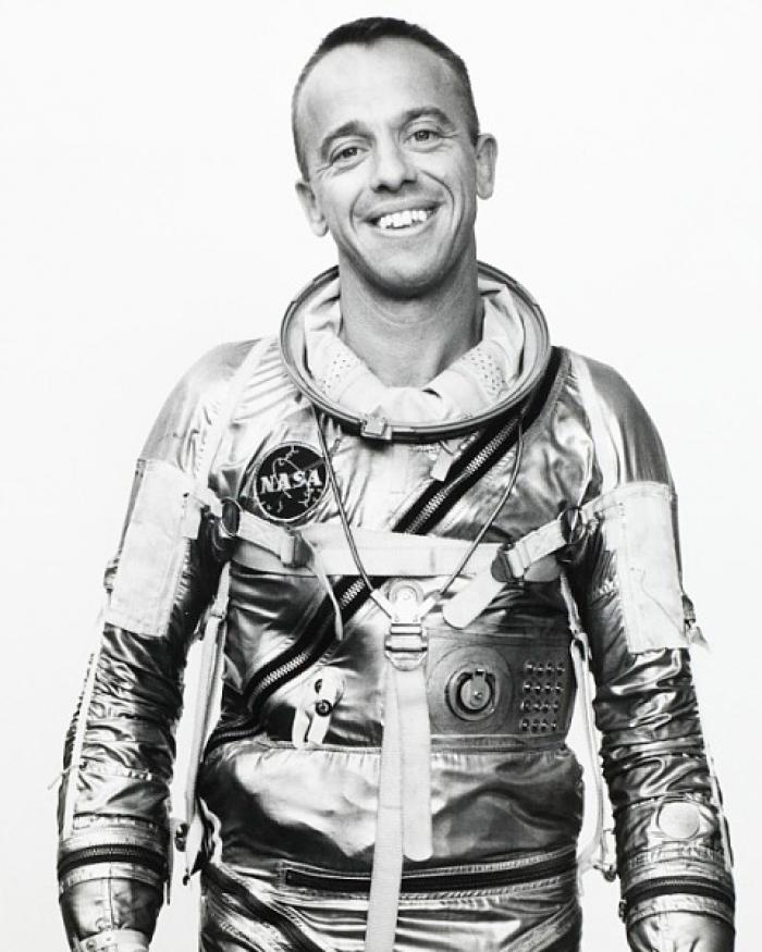 Alan Shepard, in his shiny Mercury spacesuit, smiles at the camera.