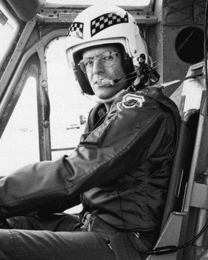 A helicopter pilot in a large helmet stares at the camera from inside a cockpit.