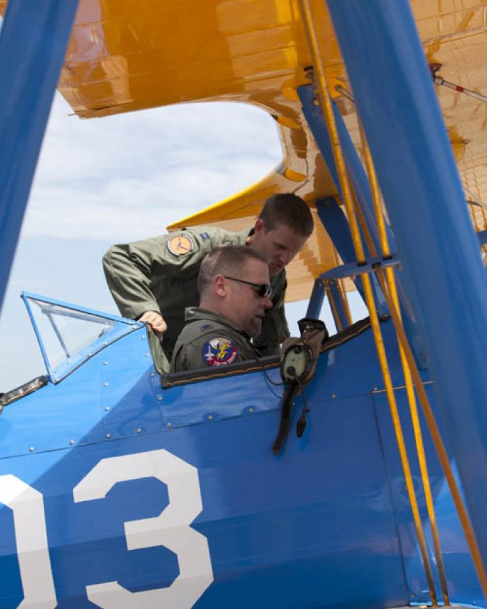 Capt. Matt Quy shows modern military curator Dik Daso how to use safety belts in the cockpit