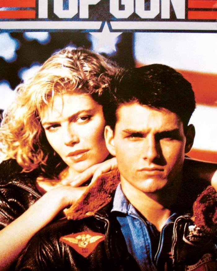 A man and a woman stare into a camera in front of a star-spangled background.