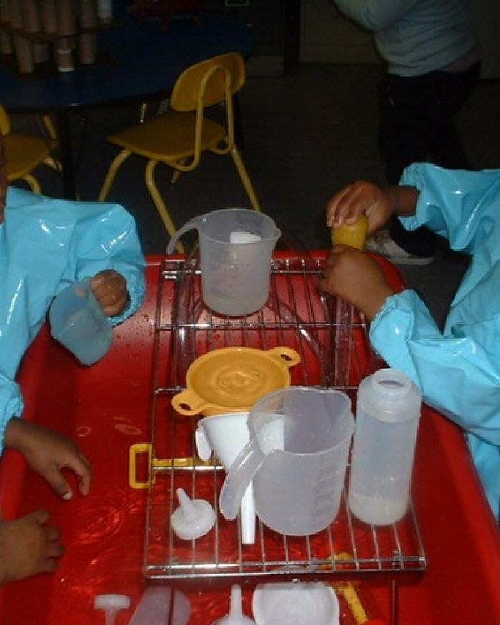 Preschoolers play at a water table.