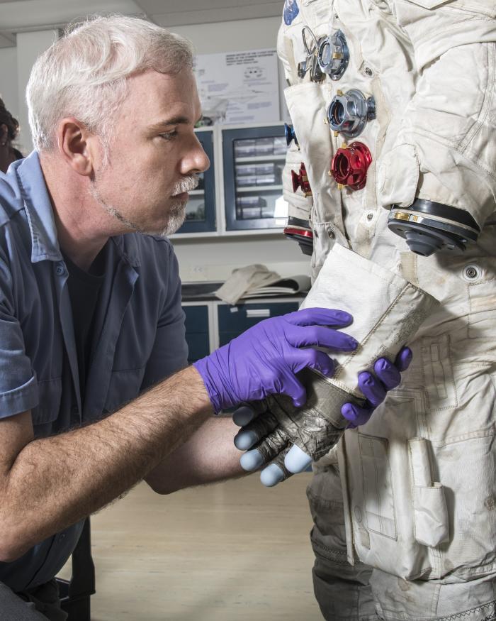 Exhibits Specialist Adam Bradshaw with the white beta cloth lunar spacesuit
