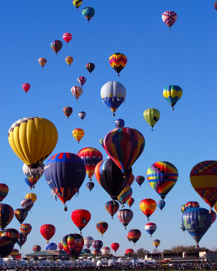 Many multicolored balloons float in the air.