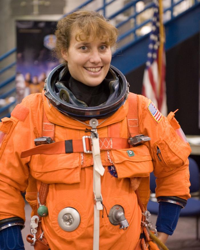 Astronaut Dottie Metcalf-Lindeburger stands in an orange space suit