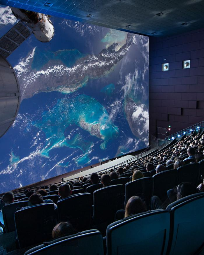 Shot of an IMAX movie screen with viewers seated in the theater.