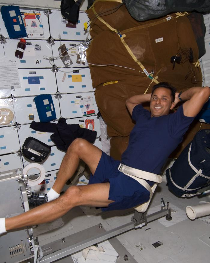Astronaut strapped into cycling equipment while in space.