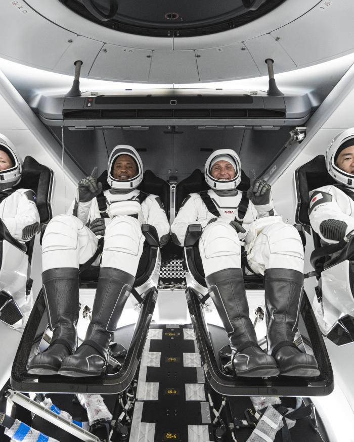 Four astronauts in space suits.