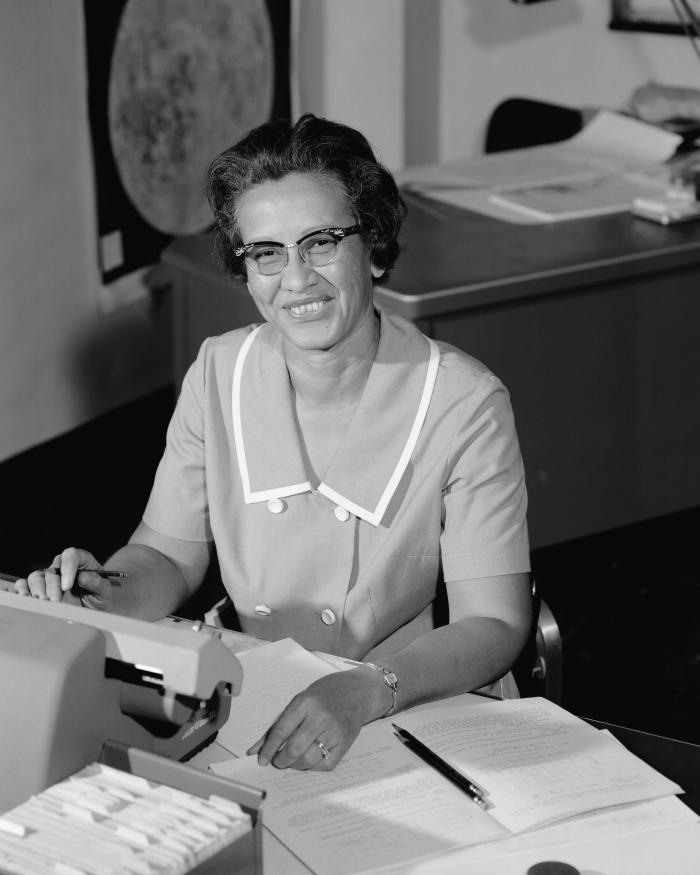 A black and white photo of an African American woman looking up from her desk smiling.