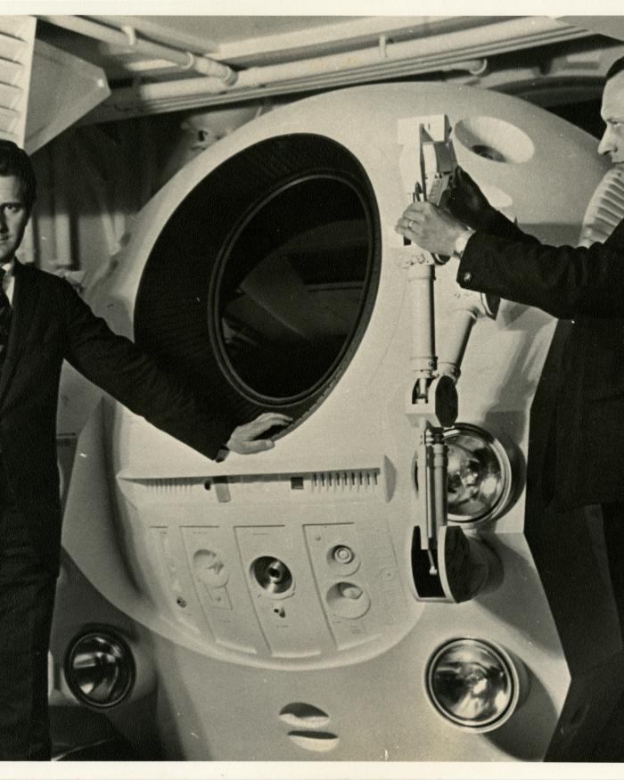 Frederick I. Ordway III (left) and Harry Lange (right) pose with an EVA Pod in the Discovery One pod bay interior set of the motion picture 2001: A Space Odyssey
