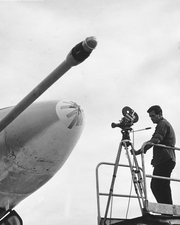 A black and white photograph of a man on a lift filming a battle damaged plane.