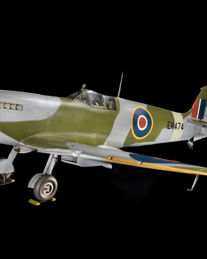Overall, three-qaurter side view of green and blue Spitfire aircraft