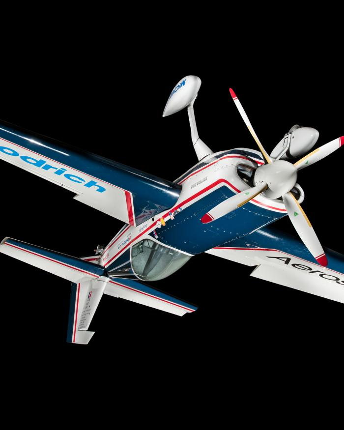 Blue and white monoplane with red trim and sponsor logos, hanging inverted