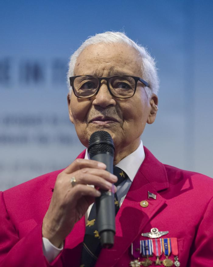 Man wearing red Tuskegee Airman jacket holding microphone