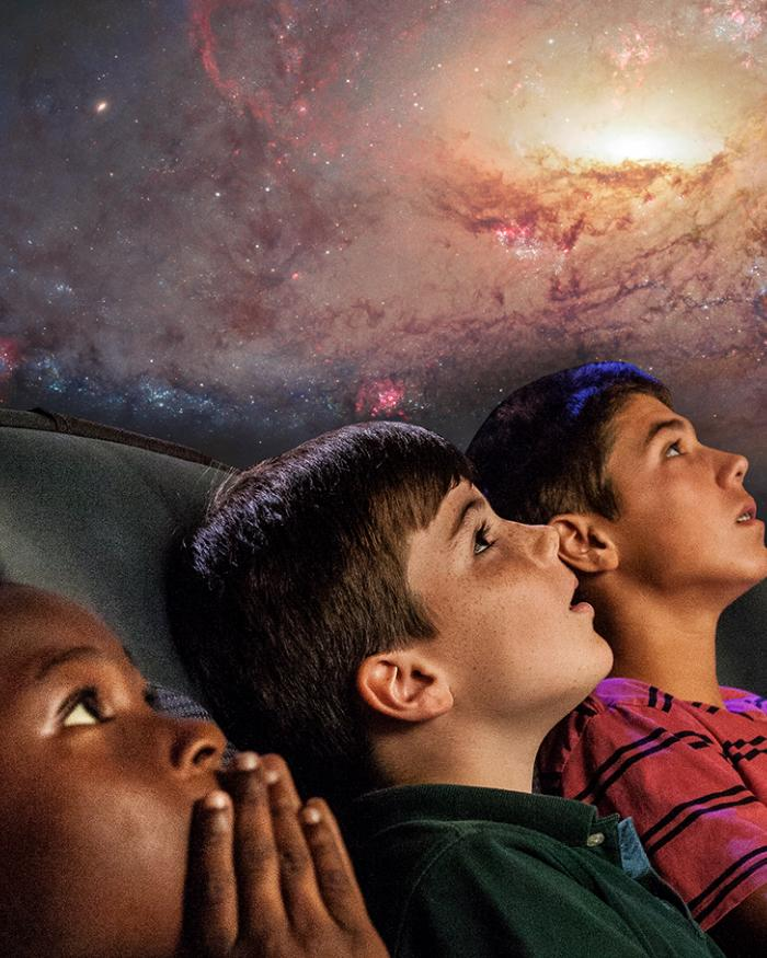 Three boys look up at a planetarium show that is above their heads.