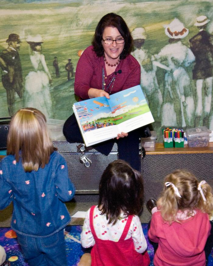 A storyteller reads to a group.