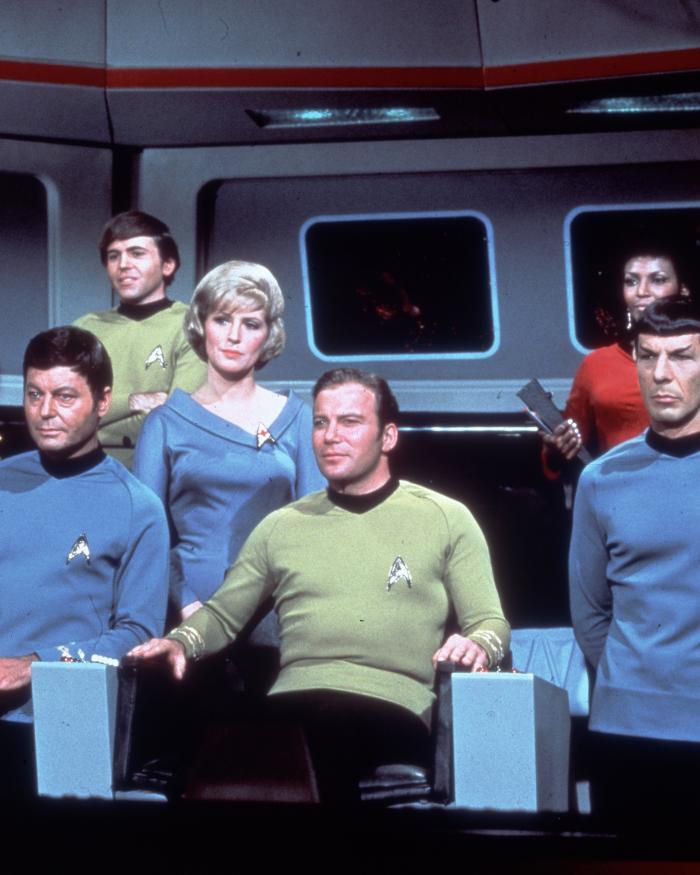Star Trek cast stands on bridge of Starship Enterprise.