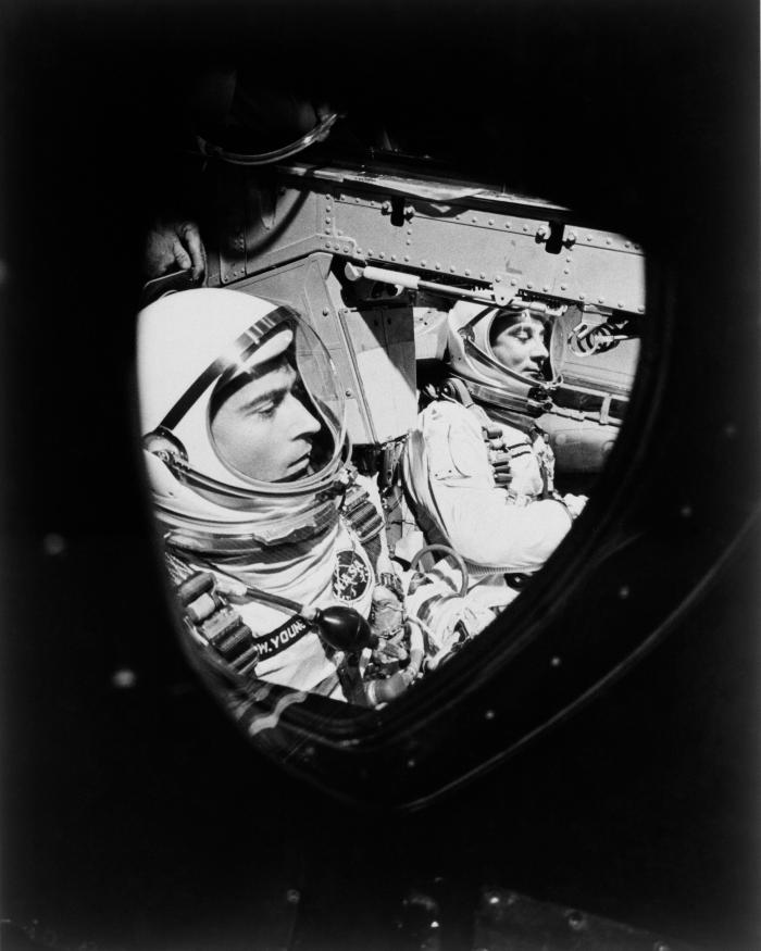 This view of astronauts John W. Young (left), pilot, and Virgil I. Grissom, command pilot, was taken through the window of the open hatch on Young's side of the Gemini-Titan 3 spacecraft just before the hatches were closed in readiness for their three-orb