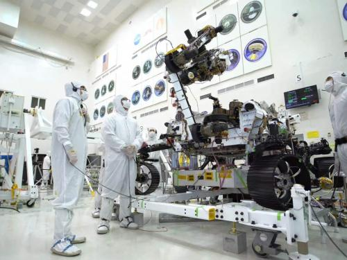 Three people in white protective suits work on rover