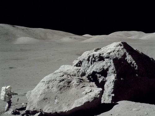An astronaut by a huge rock on the moon.