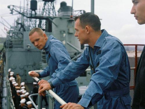 Three white men lean over the railing of a ship.