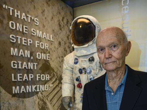 Man in blue shirt stands in front of exhibit case with spacesuit inside.