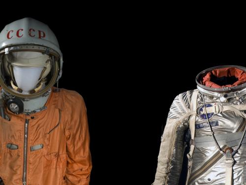Two spacesuits side by side. One has a helmet and is nylon. The other is metallic.