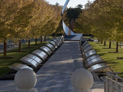 Tree lines path with a vertical swooping metal sculpture at the end