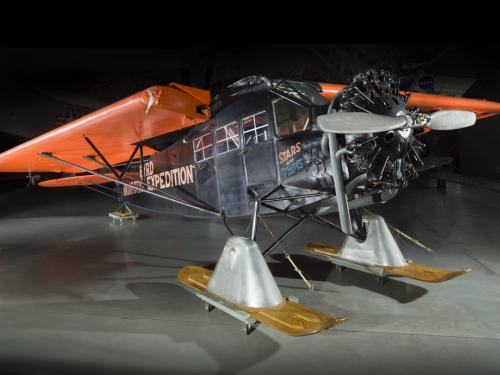 Black and orange painted plane with landing skis.
