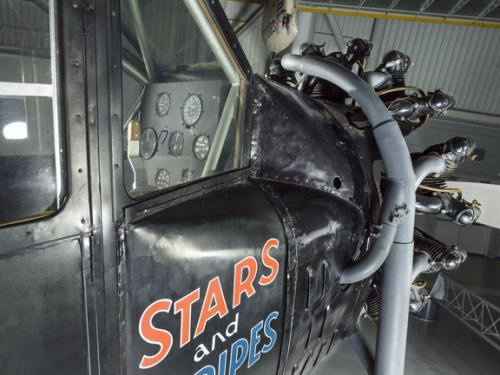 View of the cockpit and engine of an airplane. The words Stars and Stripes are painted on the side of the airplane.