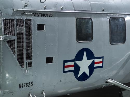 United States Coast Guard insignia painted on the fuselage of a silver helicopter.