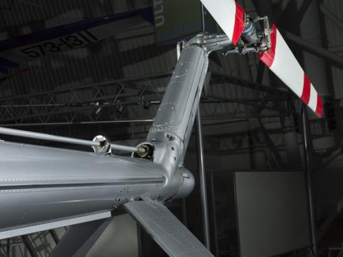 View of a red and white painted tail rotor on a helicopter.
