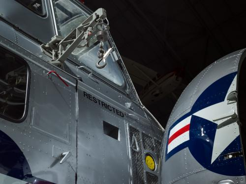 View of a cargo hook and a nose of a helicopter. The nose is open and painted on is the United States Air Force insignia.