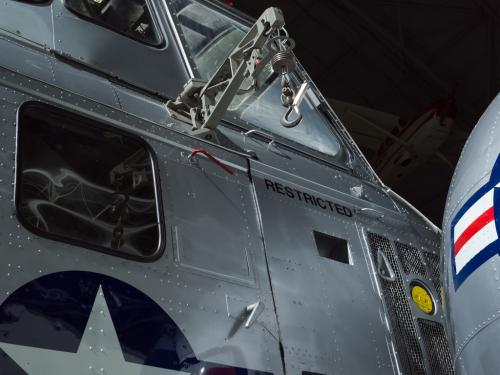 View of a cargo hook, windows, and the word restricted painted on the helicopter.