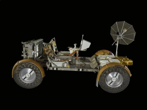 Side view of a four-wheel battery powered vehicle with attached antenna.