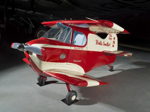 Side view of a red and white painted smallest man-carrying plane.