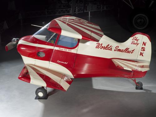 Side view of red and white painted smallest man-carrying plane.