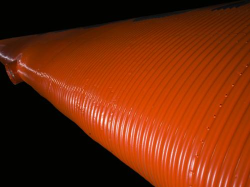 Close up image of an orange wing and light of a plane.