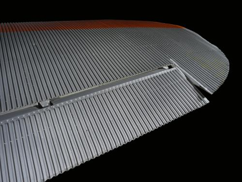 Close up view of a silver and orange painted wing of an airplane.
