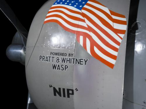 View of an engine with an American flag logo on an airplane.