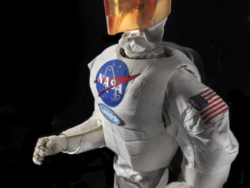 Upper body of a robot with arms, chest with a NASA logo, and an orange face cover.