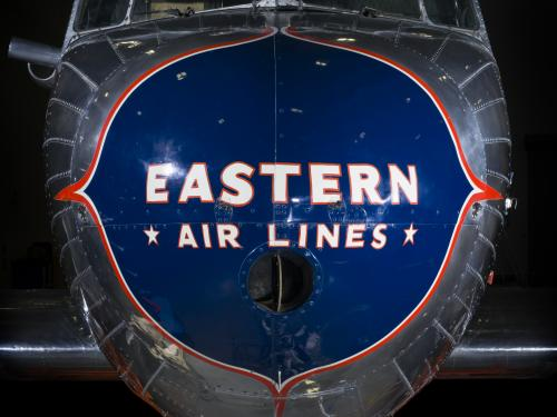 "Close up of the nose of the plane. Painted on a blue nose is the phrase ""Eastern *Air Lines."""