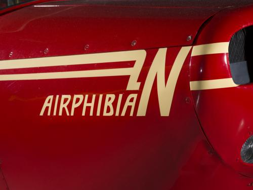 Logo of a plane called Airphibian. The plane is painted red and the logo is painted tan.