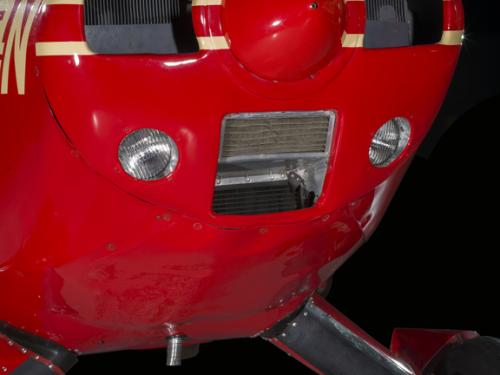 Close up of the nose of a red pained plane.