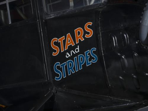 The words Stars and Stripes are painted orange and blue on the side of an airplane.