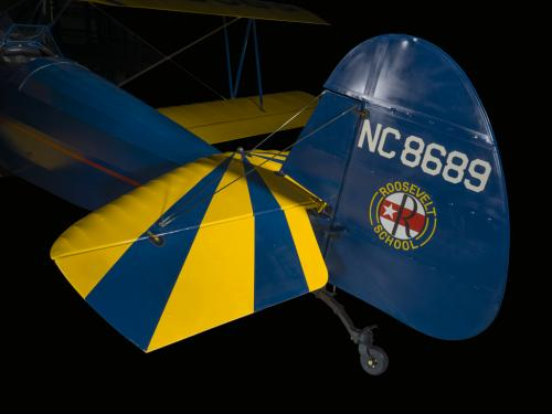 Rudder attached to a yellow and blue painted aircraft. NC8689 is painted on the rudder.