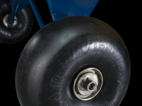 Close of of a tire and blue painted landing gear of a airplane.
