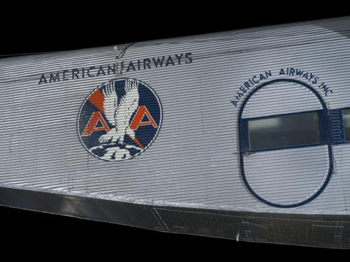 Silver painted fuselage of an airplane. Painted on to the fuselage is an American Airways logo.