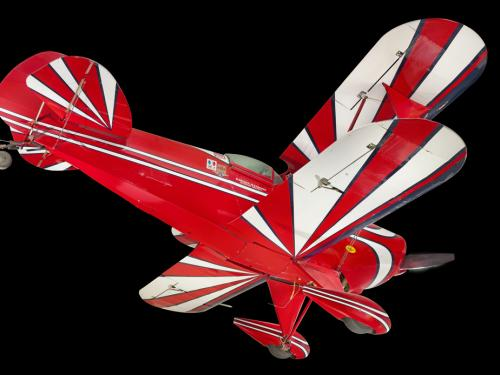 View of the undercarriage of a red, white, and blue painted aerobatic biplane.