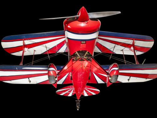 View of the landing gear of a red, white, and blue painted aerobatic biplane.